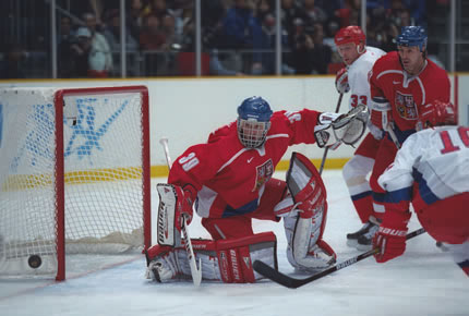 Czech Republic cage master DOMINIK HASEK turns aside a Russian shot as PAVEL BURE (10) lurks in the final Group B game of the round robin stage at the 1998 Winter Games from Nagano. Russia won this match, 2-1.