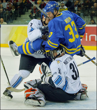 Finnish defenseman AKI-PETTERI BERG (7) spills Swedish forward FREDRIK MODIN (33) over top of goaltender ANTERO NIITYMAKI in the Gold Medal Match at the 2006 Winter Olympic Games in Turin, Italy. The Finns fell at the final hurdle 3-2 to their Nordic neighbors and arch-rivals. Finland have earned two silver and two bronze medals at the Olympics.