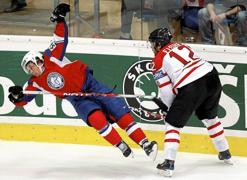 Norway's MATS ZUCCARELLO AASEN is sent flying by Canada's MIKE FISHER (12) at the 2009 IIHF World Championships in Switzerland. Canada defeated Norway 5-1 in the qualification round. Aasen, who had three goals in Switzerland, has appeared twice at the World Championships (13 ga, 4 go 0 as, 4 pts) for Norway.