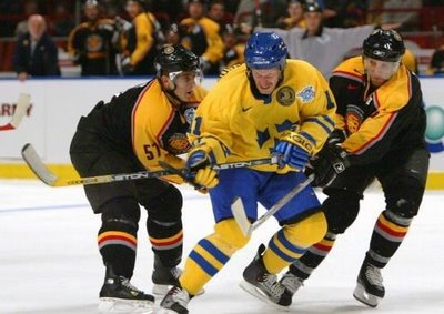 DANIEL ALFREDSSON (11) fights his way through two defenders in Sweden's 5-2 defeat of Germany at the 2004 World Cup of Hockey in Stockholm. Alfredsson had two assists in the contest. The 37-year-old Ottawa Senators right wing has been chosen to his fourth Olympic ice hockey squad for Sweden.