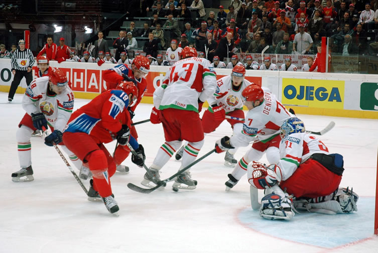Belarus forward ALEXEI UGAROV (18), left, and defenseman VLADIMIR DENISOV (7), right, fish for the puck in the skates of teammate VIKTOR KOSTYUCHENOK (43) as goalie ANDREI MEZIN and forward ANDREI STAS (23) await in the quarterfinal round of the 2009 IIHF World Championships in Switzerland. The names of all five players appear on the Olympic roster released by the Belarus Ice Hockey Federation Dec 23.