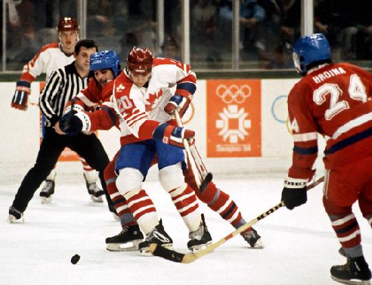 Canadian center CAREY WILSON (20) is hampered from behind by his counterpart, Czechoslovak center VLADIMIR RUZICKA, as JIRI HRDINA (24) looks on at the 1984 Winter Olympic Games in Sarajevo, Yugoslavia. Czechoslovakia, the eventual silver medalists, defeated Canada 4-0 on the final day of Group B round-robin play. Wilson, who played two years of college hockey at Dartmouth before spending the season prior to Sarajevo in Finland's elite league with IFK Helsinki, scored three goals on opening day in Canada's 4-2 defeat of the defending gold medalist United States.