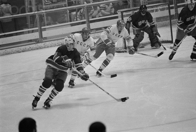 The United States attempts to move the puck out of the defensive zone as Soviet forecheckers give chase at the 1972 Winter Olympic Games in Sapporo, Japan. The USSR, on their way to a third consecutive Olympic gold medal, defeated the USA 7-2. Guarding the net for the Americans against the Soviets is MIKE CURRAN (30).