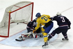 Sweden's LOUI ERIKSSON (21) fights off U.S. defenseman JACK JOHNSON and shoots past goalie ROBERT ESCHE in the bronze medal match at the 2009 IIHF World Championships. Sweden defeated the United States 4-2.