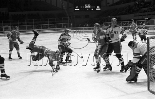 ANATOLI FIRSOV (falling, center) fires a shot into the pads of Finland goaltender URPO YLONEN at the 1968 Winter Olympic Games in Grenoble, France. As the scoreboard in the background indicates, a little over seven minutes have been played (Olympic hockey clocks count time up, not down as in the NHL) in the first period with the Soviets already leading 3-0. On the opening day of the final round-robin, the Soviet Union defeated Finland 8-0 with Firsov scoring once.