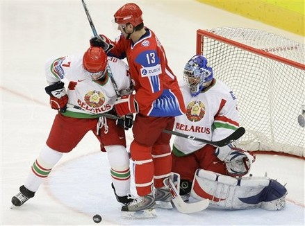 Belarus defender VLADIMIR DENISOV (7) contests a loose puck in front of goalie ANDREI MEZIN with Russian forward NIKOLAI ZHERDEV at the 2009 IIHF World Championships in Switzerland. Russia narrowly defeated the Belarus 4-3 with the only goal of the third period. Both Denisov and Zherdev spent the 2008-09 season with the New York Rangers organization; Denisov skated with the Hartford Wolf Pack of the American Hockey League.