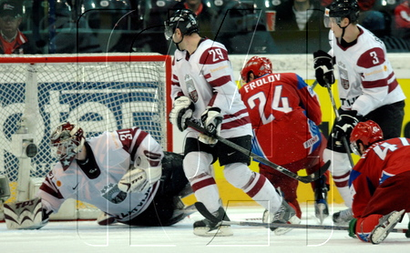 OSKARS BARTULIS (3) and AIGARS CIPRUSS (29) look on as Latvia netminder EDGARS MASALSKIS searches for the puck in the qualification round match versus Russia at the 2009 IIHF World Championships in Switzerland. Russia, the eventual champion, defeated Latvia 6-1. The two nations will meet again in Group B at the Winter Olympics this February from Vancouver.
