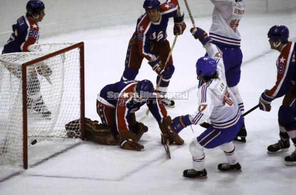 Norway's ARNE BERGSENG (15, right) signals his game-opening goal versus United States netminder BOB MASON, who has been caught out of his cage.