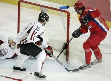 Russia's ILYA KOVALCHUK (71) stuffs the puck past Latvia goaltender ARTURS IRBE to the chagrin of defenseman KRISJANIS REDLIHS (25) in the round-robin at the 2006 Winter Olympics in Turin. Kovalchuk's second goal of the first period, here, gives Russia a 3-1 lead on their way to a 9-2 romp. In all, Kovalchuk totaled four goals for the contest.