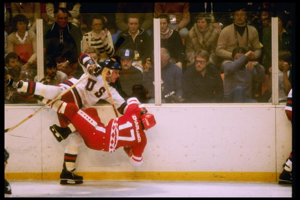 MIKE RAMSEY of the UNITED STATES delivers a devastating blow along the boards to legendary superstar VALERY KHARLAMOV (17) of the SOVIET UNION during the famous medal round match in Lake Placid, New York, at the 1980 Winter Olympic Games. The USA upset the USSR, 4-3, and went on to garner the gold medal.