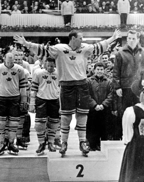 "SVEN ""Tumba"" JOHANSSON of silver-medalist Sweden on the podium at the awards ceremony for the 1964 Winter Olympic Games in Innsbruck, Austria. To Johansson's left is Boris Mayorov, the captain of the champion Soviet Union squad. Johansson, who attended the Boston Bruins' training camp in the fall of 1957, was tournament top scorer with both 8 goals and 11 points for Tre Kronor."
