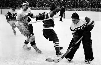 Goaltender NIKOLAI PUCHKOV (far right) plays the puck for the Soviet Union at the 1954 IIHF World Championships in Stockholm. With Pushkov between the pipes in Sweden, the USSR captured the annual IIHF title on their debut at a major international event.