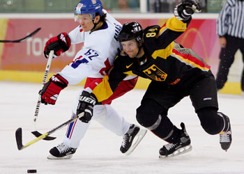 PATRIK ELIAS (62) of the Czech Republic competes for the puck with Germany's DENNIS SEIDENBERG (84) at the 2006 Winter Olympic Games in Turin, Italy.