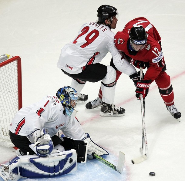 Swiss goaltender JONAS HILLER and defenseman BEAT FORSTER (29) hold off Canada's ERIC STAAL (12) at the 2007 IIHF World Championships in Moscow. Hiller has never appeared at the Winter Olympic Games for Switzerland before.