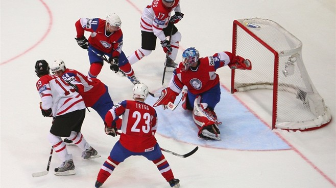 CANADA (white shirts, black pants) confront the goal of NORWAY (red shirts, blue pants).