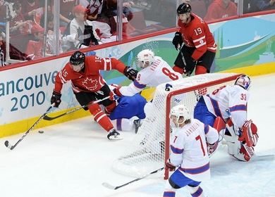 German-born DANY HEATLEY, a one-time star for the University of Wisconsin, scored two goals in Canada's 8-0 rout of Norway at the 2010 Winter Olympics. Here, Heatley is hamped by Norway's MADS HANSEN (8) as San Jose Shark JOE THORNTON (19) supervises for Canada. (Matthew Manor/HHOF-IIHF Images)