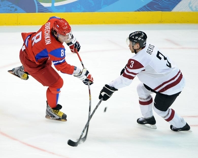 Russia's ALEXANDER OVECHKIN (8) has his shot snuffed by Latvian defenseman ARVIDS REKIS at the 2010 Winter Olympics. Ovechkin scored a pair of goals as Russia overpowered Latvia 8-2 on opening day at the Vancouver Games. (Matthew Manor/HHOF-IIHF Images)