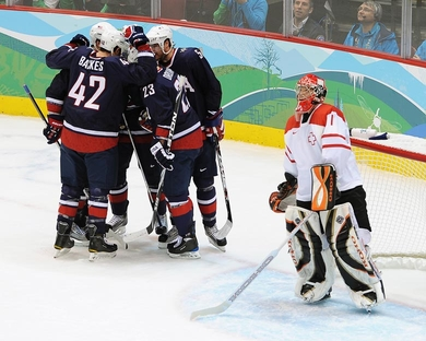 Switzerland goaltender JONAS HILLER (1) looks up at the scoreboard to see 2-0 registered for the United States after DAVID BACKES (42) scored moments earlier. (Matthew Manor/HHOF-IIHF Images)