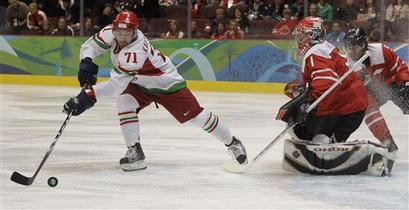 Belarus forward ALEXEI KALYUZHNY (71) backhands his shot after Switzerland goaltender JONAS HILLER (1) mishandled the puck in the opening minute of play. (Julie Jacobson/AP)
