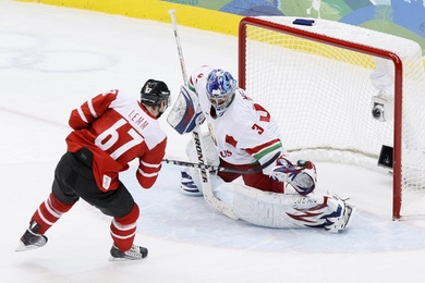 Switzerland's ROMANO LEMM (67) puts the game-winning penalty-shot past Belarus goaltender ANDREI MEZIN in the quarterfinal qualification round of the 2010 Winter Olympic Games in Vancouver. Switzerland defeated Belarus 3-2 in the shootout following ten minutes of overtime. It was Lemm who had levied the winner against Norway in Switzerland's prior match. (Jukka Rautio/HHOF-IIHF Images)