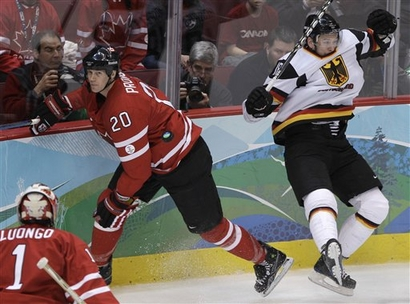 Canada defenseman CHRIS PRONGER (20) skates off after hitting Germany forward KAI HOSPELT (18) as Canadian goaltender ROBERTO LUONGO (1) looks on at the 2010 Winter Olympic Games in Vancouver. (Matt Slocum/AP photo)