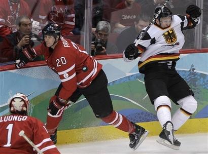 Canada defenseman CHRIS PRONGER (20) skates off after hitting Germany forward KAI HOSPELT (18) as Canadian goaltender ROBERTO LUONGO (1) looks on at the 2010 Winter Olympic Games in Vancouver. (Matt Slocum/AP photo)