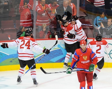 Russia's VIKTOR KOZLOV (52) skates away as Canada's RYAN GETZLAFF (51) gets a hug from DAN BOYLE (22) while Corey PERRY (24) and DUNCAN KEITH (2) look to join the celebration. Getzlaff's goal just 2:21 into the game sparked Canada to a surprisingly-simple 7-3 quarterfinal romp over Russia at the 2010 Winter Games in Vancouver. (Matthew Manor/HHOF-IIHF Images) 