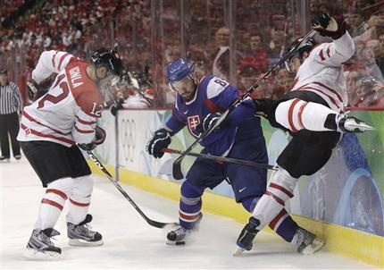 Canada's JAROME IGINLA (12) fishes for the puck in the skates of Slovakia's MARTIN CIBAK (8) as Canada's SHEA WEBER (6) wipes out at the boards in Vancouver. (Matt Slocum/AP)