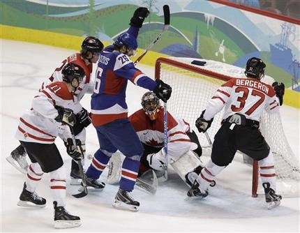 Slovakia's MICHAL HANDZUS (26), with his hand high, looks down at the puck he just batted out of mid-air past Canada goaltender ROBERTO LUONGO to trim the deficit to a single goal late in the Olympic semifinal match at Canada Hockey Place. PATRICK MARLEAU (11), DUNCAN KEITH (2) and PATRICE BERGERON (37) are the Canadians who cannot help the seated Luongo. (Julie Jacobson/AP)