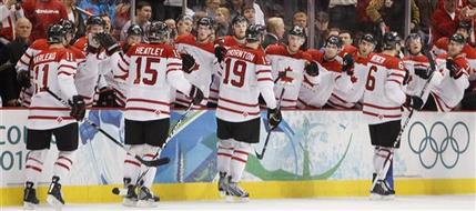 PATRICK MARLEAU (15), at the back of the pack, and the rest of the goal-makers greet Canada's bench after breaking the ice at the 2010 Winter Olympic semifinal match versus Slovakia in Vancouver. DANY HEATLEY (15) had done yeoman work along the boards in the offensive zone; SHEA WEBER (6), leading the procession, generated the point shot for Marleau to deflect. (Gene J. Puskar/AP)