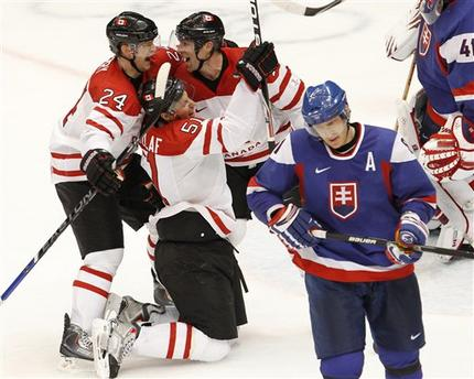 Canada's RYAN GETLZAFF (51) celebrates his goal from his knees while COREY PERRY (24) and BRENDEN MORROW (10) elate in the semifinals of the 2010 Winter Olympics at Vancouver. Getzlaff's goal ultimately proved to be the game-winner. Meanwhile, star forward MARIAN HOSSA (81) skates away for Slovakia. (Ryan Remiorz/The Canadian Press)