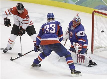 Canada's BRENDEN MORROW (10) watches the shot of the not-pictured RYAN GETZLAFF go past the left shoulder of Slovakia goaltender JAROSLAV HALAK with defenseman ZDENO CHARA (33) in front. Getzlaff's late second period goal gave Canada a 3-0 lead in the Olympic semifinal at the Vancouver Games. (Julie Jacobson/AP)  