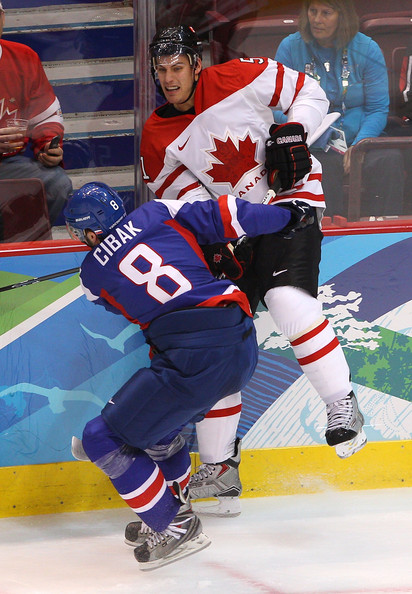 Slovakia's MARTIN CIBAK (8) of Russian club Spartak Moscow checks Canada's game-winning-goal scorer RYAN GETLZAFF (51) against the boards in the Olympic semifinals from Vancouver. Cibak played 154 NHL games in four seasons with the Tampa Bay Lightning organization before signing to play in Sweden to start the 2006-07 schedule. The 29-year-old center joined Spartak this season from Swedish club SK Sodertalje. (Cameron Spencer/Getty Images)