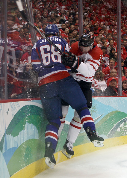 As the ice shavings fly, the Slovak defenseman Jurcina and Canadian forward Heatly converge in a jarring collision along the boards at the Olympic semifinals in Vancouver. (Bruce Bennett/Getty Images)