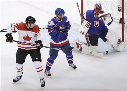 Canada's PATRICK MARLEAU (11) deflects the puck down and through the five-hole of Slovakia goaltender JAROSLAV HALAK to give Canada a 1-0 lead thirteen and a half minutes into the Olympic semifinal in Vancouver. LUBOMIR VISNOVSKY (17) defends in vain for the Slovaks. (Chris O'Meara/AP)