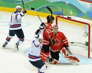United States forwards ZACH PARISE (9) of the New Jersey Devils and PAUL STASTNY (26) of the Colorado Avalanche signal BRIAN RAFALSKI's strike just 41 seconds into the match versus host nation Canada at the 2010 Winter Olympic Games in Vancouver. Dejected are Canada's goalie, MARTIN BRODEUR of the New Jersey Devils, and one-time New Jersey Devils defenseman SCOTT NIEDERMAYER (27), now of the Anaheim Ducks. (Matthew Manor/HHOF-IIHF Images)