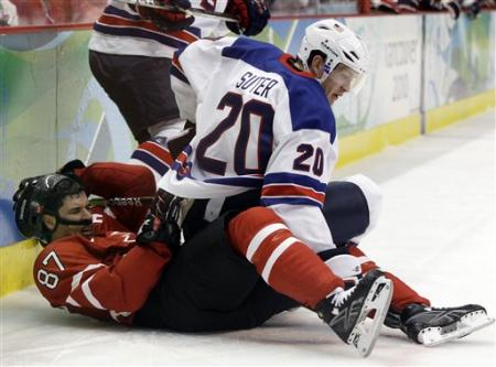 Canada superstar SIDNEY CROSBY (87) is clobbered at the boards on home ice by United States defenseman RYAN SUTER (20) at the 2010 Winter Olympic Games in Vancouver. (AP photo)