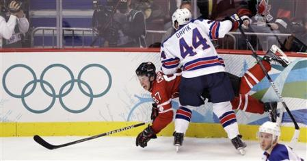 Teammates on the Stanley Cup champion Pittsburgh Penquins notwithstanding, Canada superstar SIDNEY CROSBY (87) is punished along the boards by United States defenseman BROOKS ORPIK at the 2010 Vancouver Games. (AP photo)