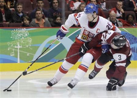 Czech Repbulic captain PATRIK ELIAS (26), hampered here by Latvian defenseman ARVIDS REKIS (3), finished off the match with an empty net goal. (AP Photo)