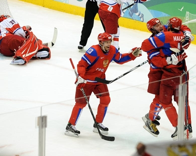 Russian forward EVGENY MALKIN (11) gets a big hug from ALEXANDER OVECHKIN (8) as PAVEL DATSYUK (13) seeks to join the celebration at the 2010 Vancouver Games. Malkin had just netted a power play goal to give the Russians a 1-0 lead in the classic confrontation of Eastern European rivals. (Matthew Manor/HHOF-IIHF Images)