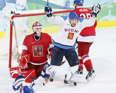 Finland's NIKLAS HAGMAN (10) raises his stick high to signal his third period goal which broke the 0-0 stalemate in the quarterfinals at the 2010 Winter Olympics. Concerned are Czech goaltender TOMAS VOKOUN and defenseman JAN HEJDA (35). Finland defeated the Czech Republic 2-0 to advance to the semifinals of the Vancouver Games. (Jukka Rautio/HHOF-IIHF Images)