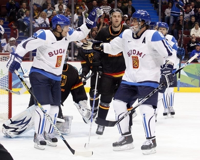 TEEMU SELANNE (8) achieves an Olympic milestone with an assist on the second goal by defenseman KIMMO TIMONEN (44). Two power play goals from Timonen helped Finland take down Germany 5-0 at the Winter Olympics in Vancouver. (Jukka Rautio/HHOF-IIHF Images)