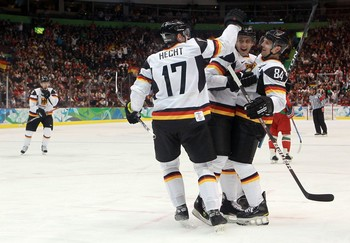 Defenseman DENNIS SEIDENBERG (84) celebrates the game's first goal and Germany's first goal of the 2010 Winter Olympic Games with MARCEL GOC (57) and JOCHEN HECHT (17) in Vancouver. (Bruce Bennett/Getty Images)