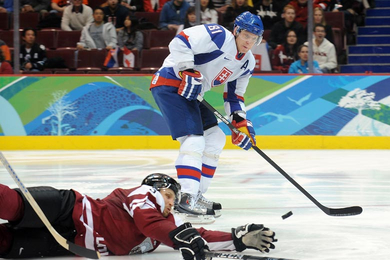 Slovakia's MARIAN HOSSA (81) receives the puck past the reach of Latvia defenseman ARVIDS REKIS (3) of German club EHC Wolfsburg. The Chicago Black Hawks star will soon deposit the pass from Josef Stumpel into the Latvian cage for his second goal in as many matches at the Vancouver Games. (Matthew Manor/HHOF-IIHF Images)