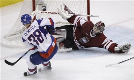 Slovakia's PAVOL DEMITRA (38) of the Olympic host city's NHL club, the Vancouver Canucks, is thwarted by Latvia goaltender EDGAR MASALSKIS at the 2010 Winter Games. Demitra scored the dramatic winner for Slovakia in their penalty-shot victory over Russia earlier in the tournament. (AP photo)