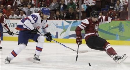 Slovakia's MICHAL HANDZUS (26) eyes the puck as Lativa defenseman GEORGIJS PUJACS (71) loses his balance at the Winter Games in Vancouver. (AP photo)