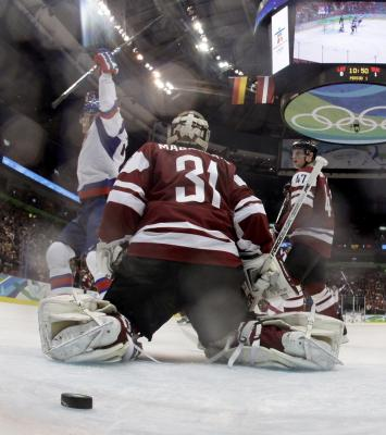 Latvian goaltender EDGARS MASALSKIS (31) is beaten yet again in Vancouver as Slovakia celebrate and Masalskis' Dynamo Riga teammate, MARTINS CIPULIS (47), is left with little consolation in Vancouver. (Reuters photo)