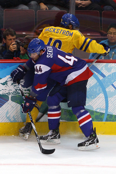 Slovakia defenseman and quarterfinal goal-scorer ANDREJ SEKERA (44) of the Buffalo Sabres squeezes Swedish center NICKLAS BACKSTROM of the Washington Capitals against the boards in Vancouver. (Cameron Spencer/Getty Images)