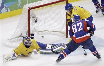 Slovakia's TOMAS KOPECKY (82) scores the goal that knocks out defending champion Sweden sends Slovakia to the semifinals of the ice hockey tournament at the 2010 Winter Olympics in Vancouver. Powerless to prevent Kopecky are Swedish defenseman NIKLAS LIDSTROM (5) and goaltender HENRIK LUNDQVIST. (Matt Slocum/AP)