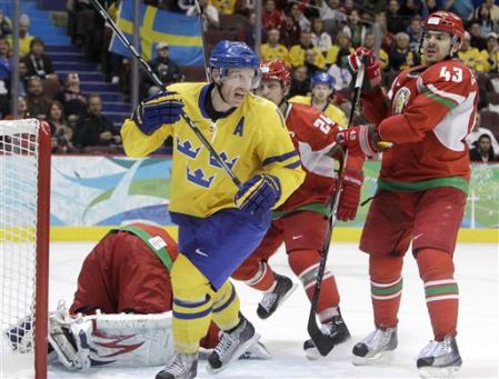 Sweden's DANIEL ALFREDSSON (11) set to celebrate as Belarussian defensemen RUSLAN SALEI (24) and VIKTOR KOSTYUCHENOK (43) already feel the frustration. (AP Photo)